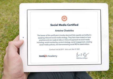 Un homme tient dans sa main une tablette dans laquelle on voit le diplôme de la certification Social Média d'HubSpot décernée à Antoine Chadufau