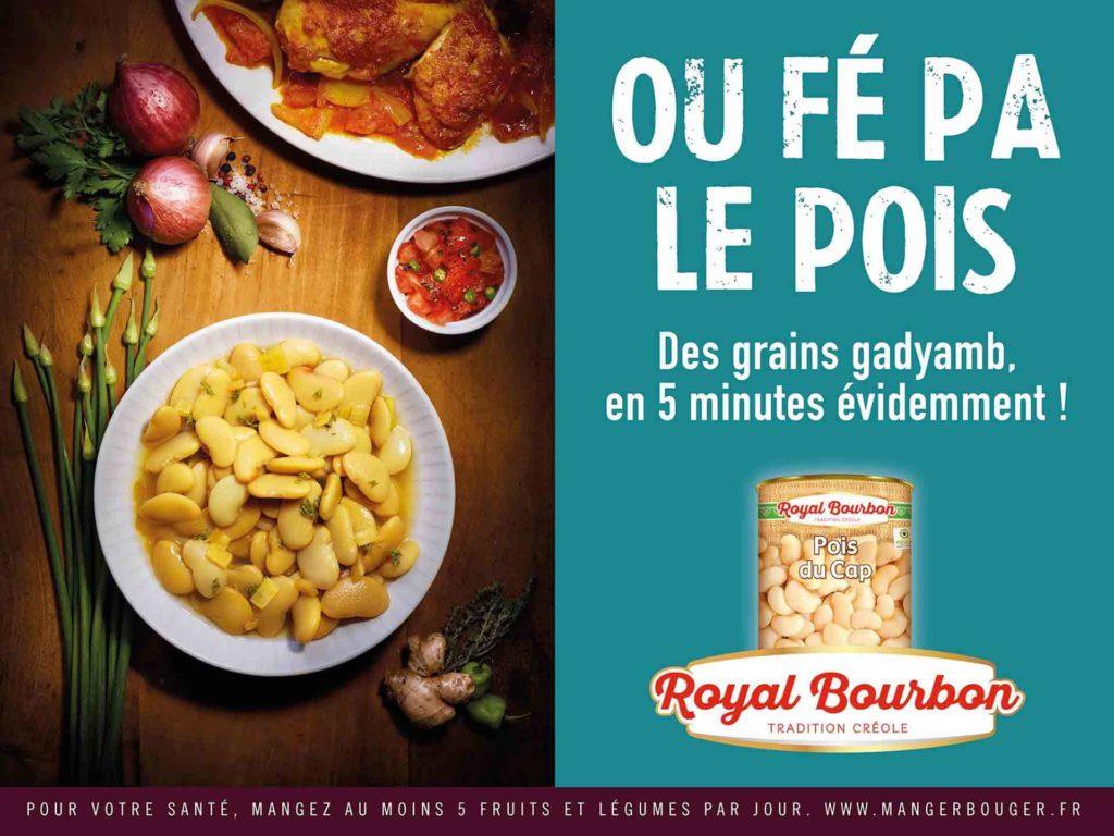 Une affiche publicitaire pour Royal Bourbon montrant a gauche une photo d eplat avec des pois du cap et à droit la boite de conserve Royal Bourbon avec les pois. Signature en créole : ou fe pa le pois.
